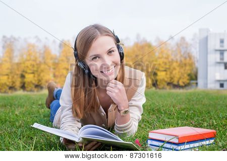 Student Listening To Headphones And Holding Opened Book