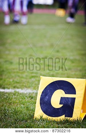 closeup of a football yard line with a sign in the foreground