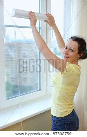 Happy woman wants to hang blinds on the window