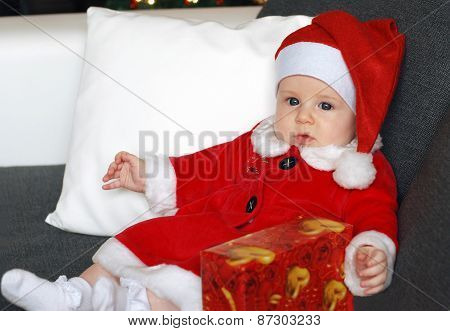 Little baby in a Santa's hat with a present