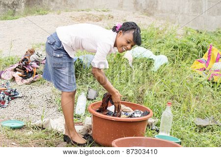 young woman doing laundry in a bowl.
