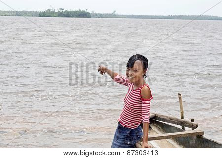 Young african woman showing the extend of water that she loves to admire.