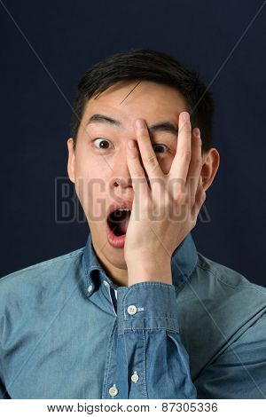 Astonished young Asian man looking at camera through his fingers