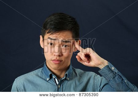 Funny young Asian man pointing his index finger against his temple as crazy sign