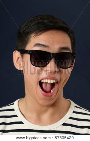 Laughing young Asian man in sunglasses