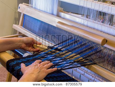 Woman Weaving A Wool Scarf On A Floor Loom