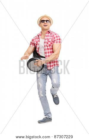 Full length portrait of a young joyful man playing on a doumbek and dancing isolated on white background