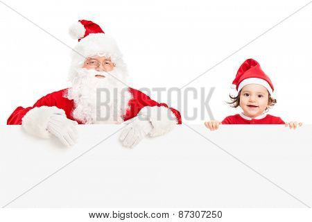 Studio shot of Santa Claus and a cute little girl standing behind a blank signboard isolated on white background