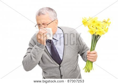 Studio shot of a senior having an allergic reaction to flowers and sneezing on a napkin isolated on white background
