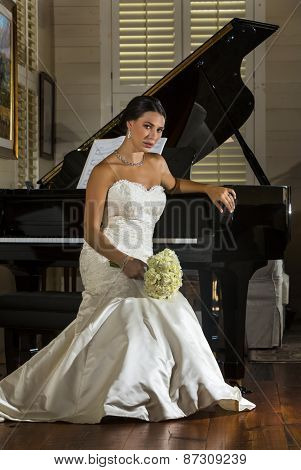 A modern bride poses indoors with a grand piano
