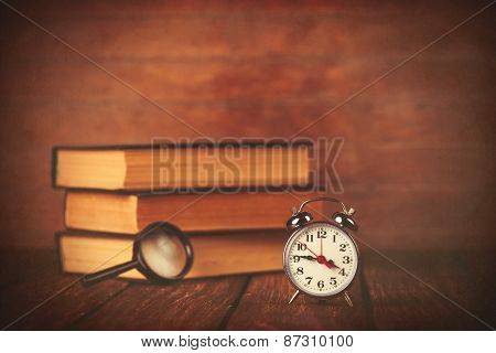 Books With Loupe And Retro Alarm Clock