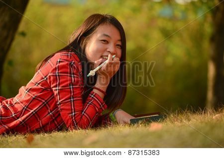 Pretty young chinese woman lie on the grass in the park and make notes in the notebook