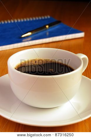 Black Coffee on Oak Desk With Pen and Notebook