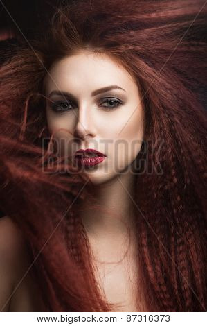 Beautiful girl with bright makeup and burgundy lips with the wind in hair. Beauty face.