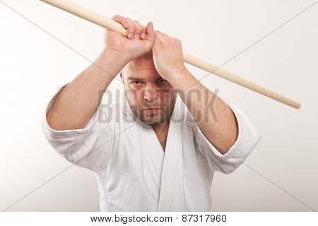 Aikido man with a stick on a light background