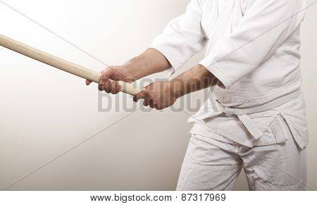 Man with wooden sword on light background