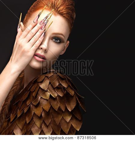 Beautiful girl in the image of the Phoenix with bright makeup, long fingernails and red hair. Beauty