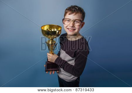 European-looking boy of ten years in glasses holding a cup in hi