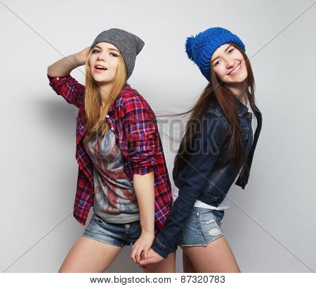 Fashion portrait of two stylish sexy hipster girls best friends, wearing cute swag outfits and hats. Over gray backround.