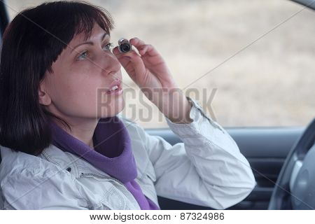 Woman wearing eyeliner in the car