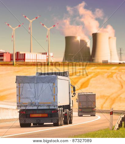 Trucks on the highway in industrial landscape. Shallow DOF and warm filtered look.