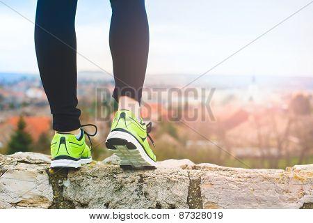 Runner feet running on the top of a hill closeup on shoe. woman fitness sunrise jog workout wellness concept.
