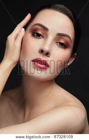 Portrait of young beautiful woman with stylish make-up touching her face