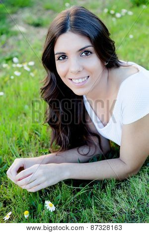 Brunette girl lying on the grass with many daisies around thinking