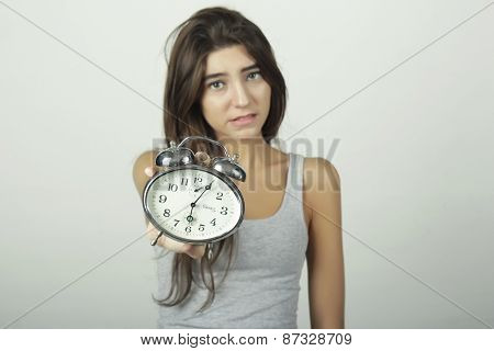 Girl showing alarm clock with worried expression.