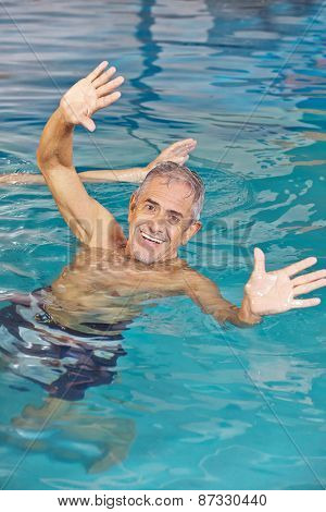 Elderly man playing water ball in swimming pool with his hands reaching out