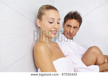 Smiling couple taking a break after sauna session in relaxation room