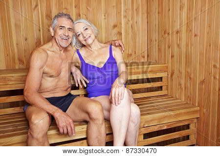 Happy senior couple sitting together in a sauna in their holidays