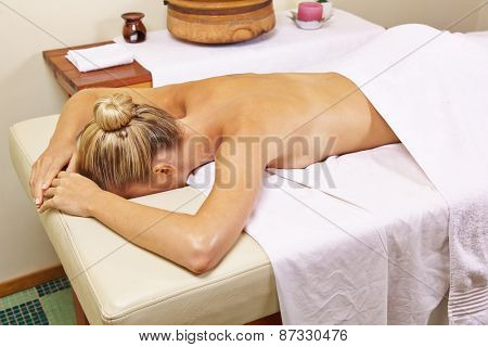 Young woman in health resort spa waiting for a back massage