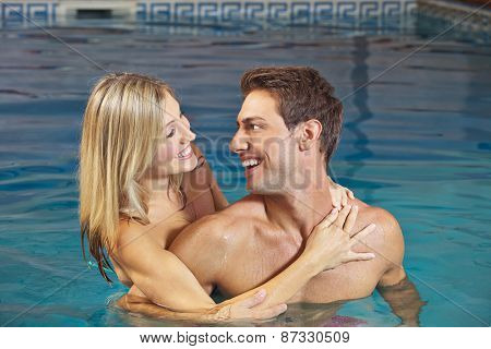 Laughing happy couple in water in a swimming pool