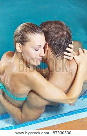 Happy couple embracing in hotel swimming pool in summer