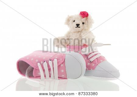 White hand made teddy bear and pink baby shoes isolated over white background