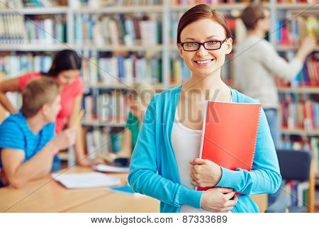 Cheerful student with copybook on background of her college friends