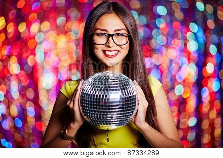 Posh girl in eyeglasses holding disco ball