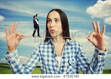 outdoor portrait of amazed woman and small man on the rope