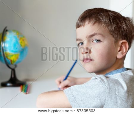 Serious Pensive Pupil Sits At Desk