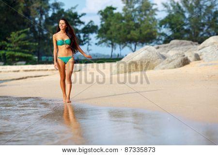 tanned brunette walking along the beach