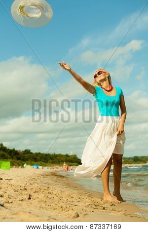 Girl Trowing Hat Up On Beach
