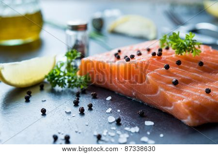 Fresh portion of raw salmon fillet with aromatic herbs on blackboard
