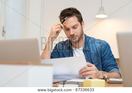 Serious young businessman looking report in office