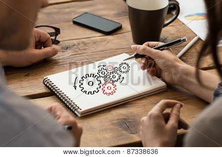Businessman and woman drawing cogwheels on paper note
