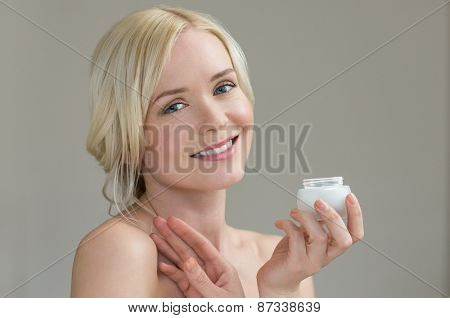 Portrait of beautiful young woman holding body's moisturizer