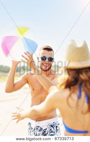 A picture of a young couple playing with a ball at the beach