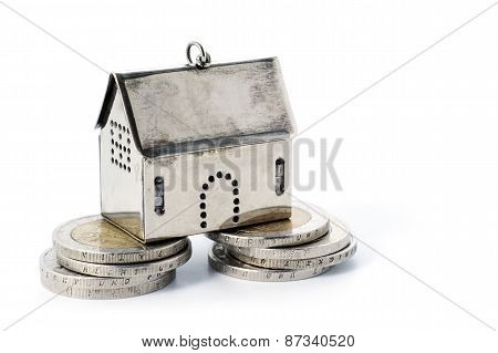 Real Estate Investment On Reliable Foundation, Small  Model House Stands On Stacks Of Coins,  Isolat
