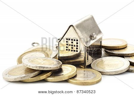 Real Estade Background, Little House In A Heap Of Coins Isolated On White