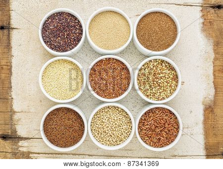 nine healthy, gluten free grains (quinoa, brown rice, millet, amaranth, teff, buckwheat, sorghum), kaniwa), top view of small round bowls against rustic barn wood